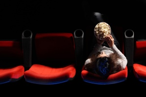a pretty young woman sitting in a row of red chairs in a theater, she eats popcorn, top view