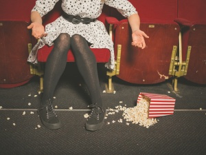 A young woman is upset about spilling her popcorn on the floor in a movie theater